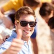 Man with friends on the beach showing thumbs up — Stock Photo