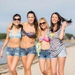 Girls in bikinis walking on the beach — Stock Photo