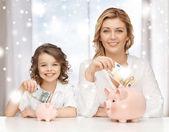 Mutter und tochter mit sparschweine und geld — Stockfoto