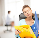 Young attractive businesswoman with folders — Stock Photo