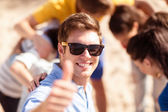 Homem com amigos na praia mostrando os polegares — Fotografia Stock