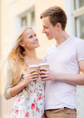 Couple in the city with takeaway coffee cups — Stock Photo