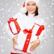 Woman in santa helper hat with many gift boxes — Foto de Stock