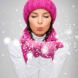 Happy woman in winter clothes blowing on palms — Stock Photo #32836621