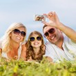 Happy family with camera taking picture — Stock Photo