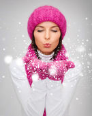 Happy woman in winter clothes blowing on palms — Stock Photo