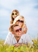 Happy family with blue sky and green grass — Stock Photo