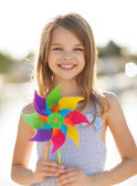 Happy girl with colorful pinwheel toy — Stock Photo