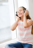 Little girl with headphones at home — Photo