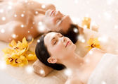 Couple in spa salon lying on the massage desks — Stock Photo