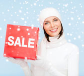 Kvinna i vinterkläder med red salu skylt — Stockfoto