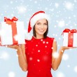 Woman in santa helper hat with many gift boxes — Stockfoto