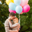 Couple with colorful balloons kissing in the park — Stock Photo #33007253