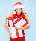 Surprised woman in santa hat with many gift boxes — Stock Photo