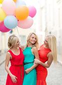 Schöne mädchen mit bunten luftballons in der stadt — Stockfoto