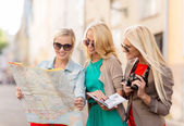 Beautiful women with tourist map in the city — Stok fotoğraf