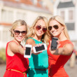 Beautiful girls with smartphones in the city — Stock Photo