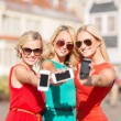 Stock Photo: Beautiful girls with smartphones in the city