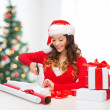 Smiling woman in santa helper hat with gift box — Stock Photo #33071483