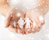 Woman hands with paper man family — Stock Photo