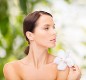 Relaxed woman with orchid flower — Stock Photo