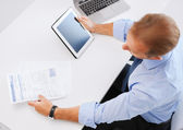 Businessman with tablet pc and papers in office — Stock Photo
