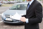 Man with car documents outside — Stock Photo