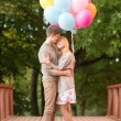 Couple with colorful balloons kissing in the park — Stock Photo #33302827