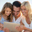 Happy family with tablet pc taking picture — Stock Photo