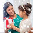 Happy mother and child girl with gift box — Stock Photo #33456103