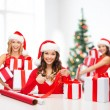 Smiling women in santa helper hat with gift box — Stock Photo