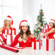 Smiling women in santa helper hat with gift box — Stock Photo #33456267