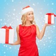 Woman in santa helper hat with many gift boxes — Stock Photo #33457843