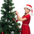 Smiling girl in santa helper hat decorating a tree — Stock Photo