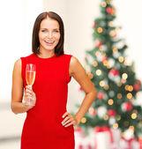 Vrouw in rode jurk met een glas champagne — Stockfoto