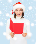 Woman in santa helper hat with blank red postcard — Stock Photo