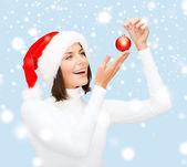 Vrouw in helper kerstmuts met Kerstmis bal — Stockfoto