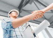 Builder with blueprint shaking partner hand — Stock Photo