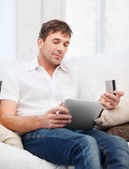 Man with tablet pc and credit card at home — Stock Photo