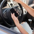 Stock Photo: Womusing phone while driving car
