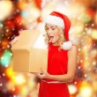 Smiling woman in santa helper hat with gift box — Stock Photo #33609307