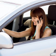 Woman using phone while driving the car — Stock Photo #33609441