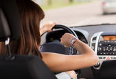 Woman driving a car and looking at watch — Stock Photo