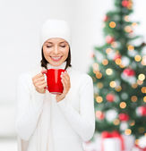 Woman in hat with red tea or coffee mug — Stock Photo