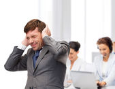 Stressed buisnessman or teacher closing ears — Stock Photo