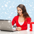 Stock Photo: Woman with gift, laptop computer and credit card