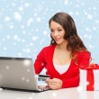 Woman with gift, laptop computer and credit card — Stock Photo #33818363