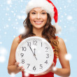 Stock Photo: Woman in santa helper hat with clock showing 12
