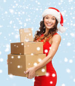 Smiling woman in santa helper hat with parcels — Stock Photo