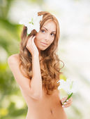 Beautiful naked woman with white lily flower — Stock Photo